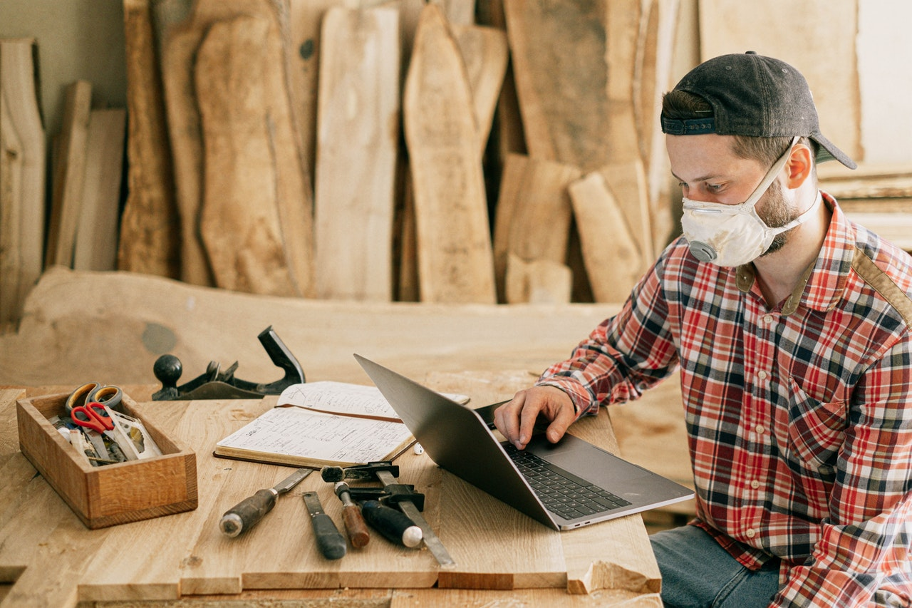Man looking at a computer in a woodshop