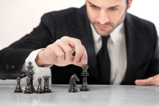 Businessman Moving Chess Pieces
