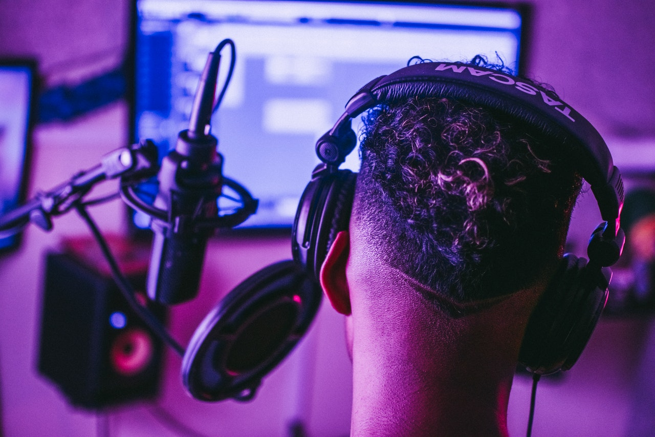 Man wearing a headset in front of a microphone