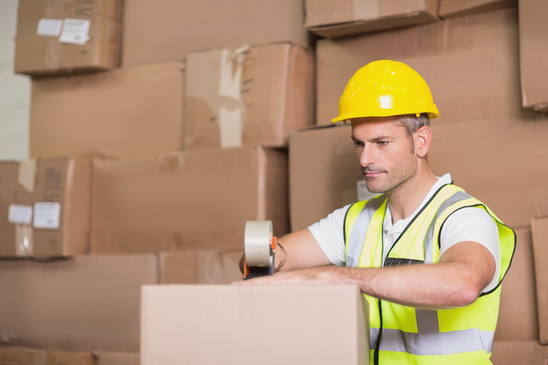 Warehouse Worker Packing a Box for Delivery