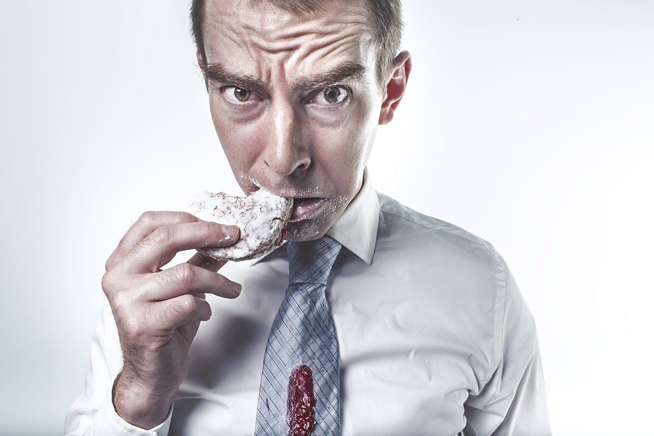 Businessman Messily Eating a Jelly Donut