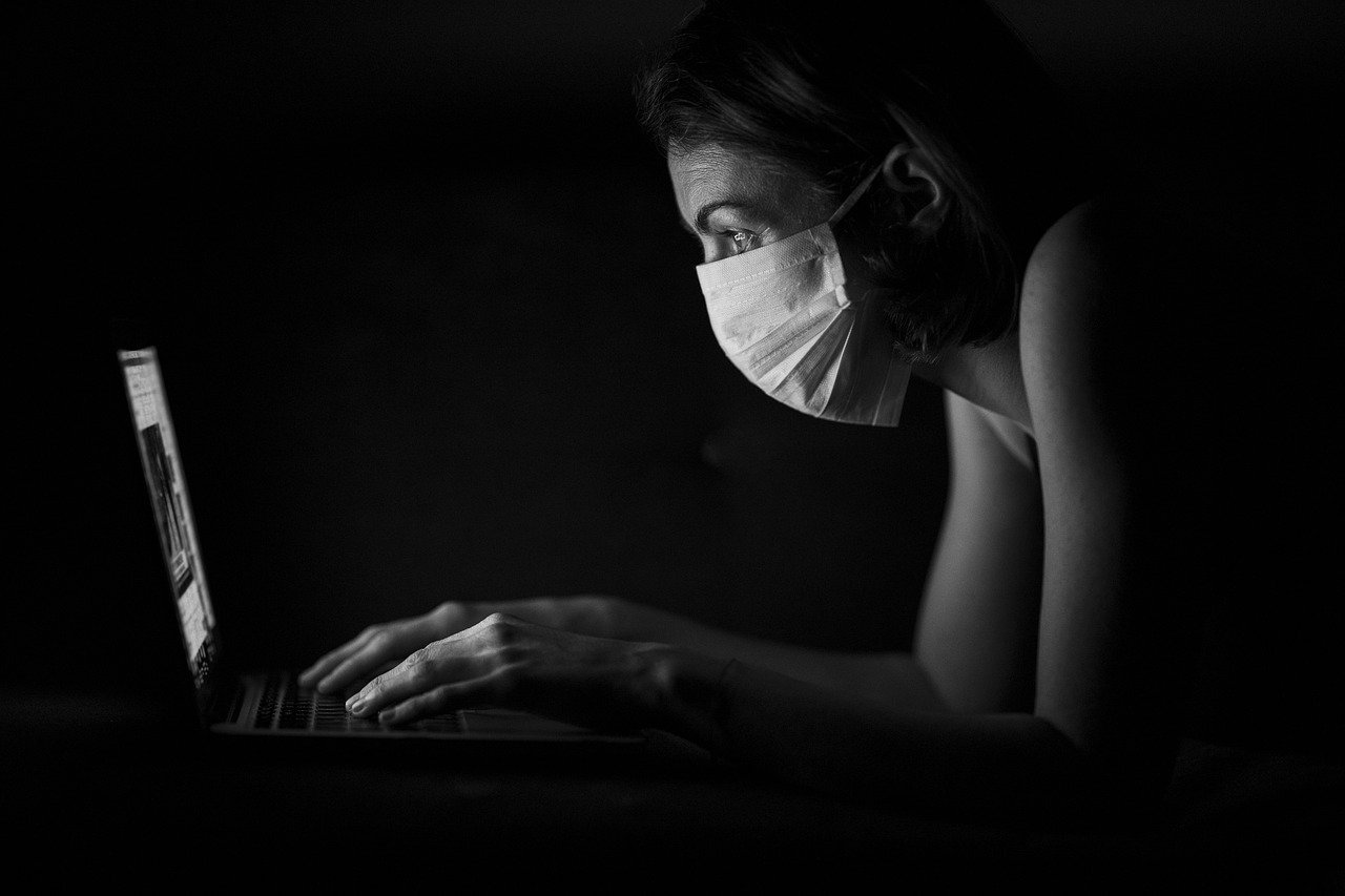 Woman Shopping Online While Wearing a Mask during the Coronavirus Pandemic