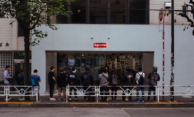 Men Waiting in Line Outside a Store