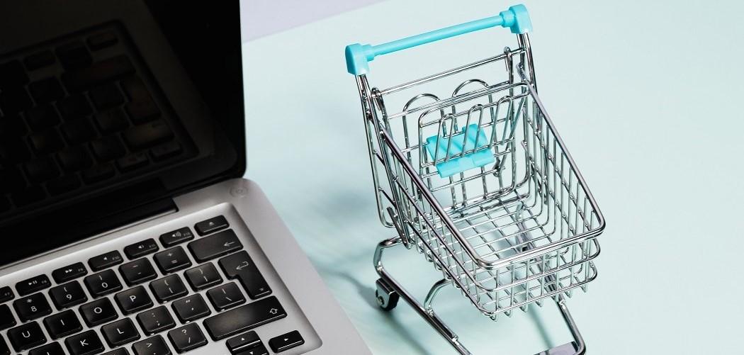 Miniature shopping cart beside laptop